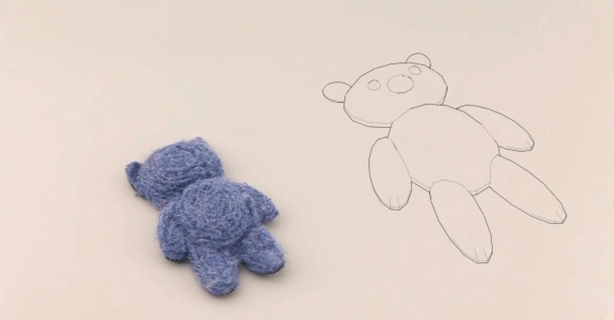One of the finished felt teddy bears, alongside its digital model