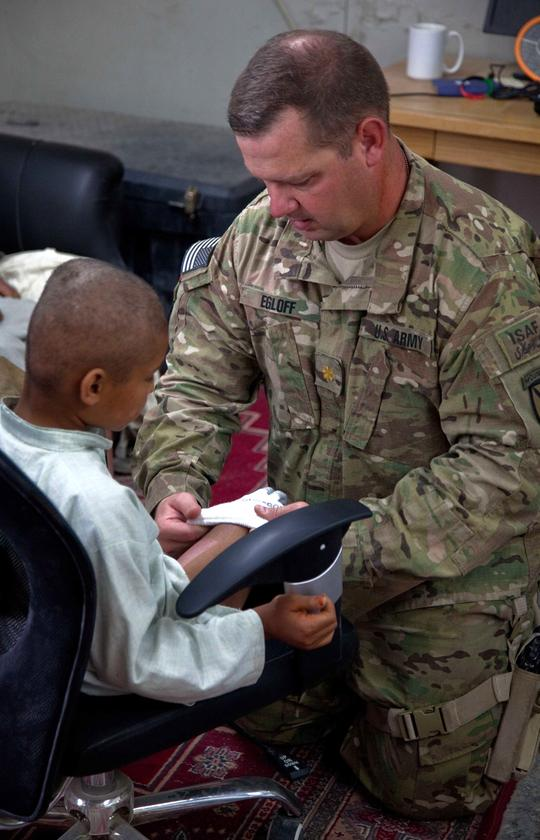 Maj. Brian Egloff puts a sock on an 8-year-old Afghan boy to aid the fitting of the prototype prosthetic leg (Image: Pfc. Justin Young)