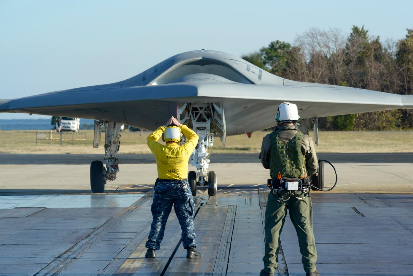 A deck operator using a wireless, handheld Control Display Unit guides the aircraft into position on a shore-based catapult (Photo: Northrop Grumman)