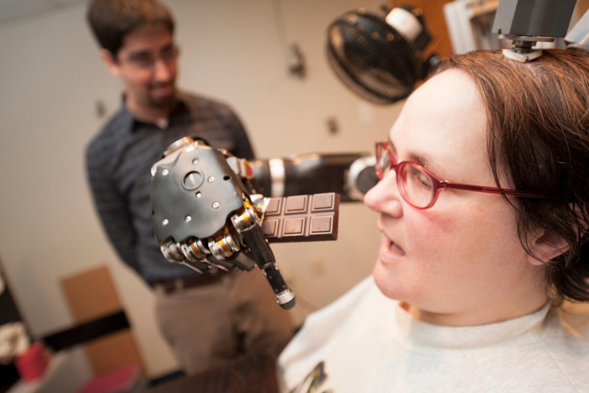 Quadriplegic Jan Scheuermann prepares to take a bite out of a chocolate bar she is guiding into her mouth with a thought-controlled robot arm while research assistant Brian Wodlinger, Ph.D., watches on (Photo: UPMC)