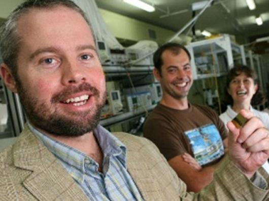 Professor Ben Eggleton (foreground) holding a photonic chip with (from left) student Neil Baker and researcher Snjezana Tomljenovic-Hanic(Photo: The University of Sydney)