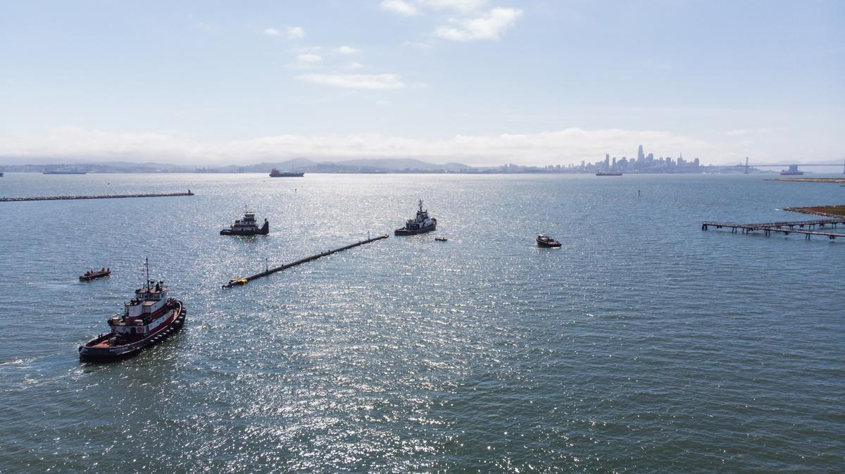 A 120-meter section of The Ocean Cleanup Project's barrier is towed out to sea