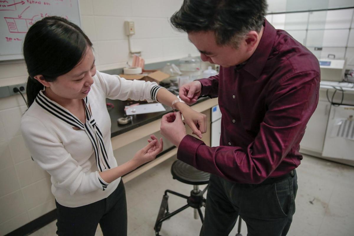 Prof. Xudong Wang fits one of the bandages around the wrist of graduate student Yin Long