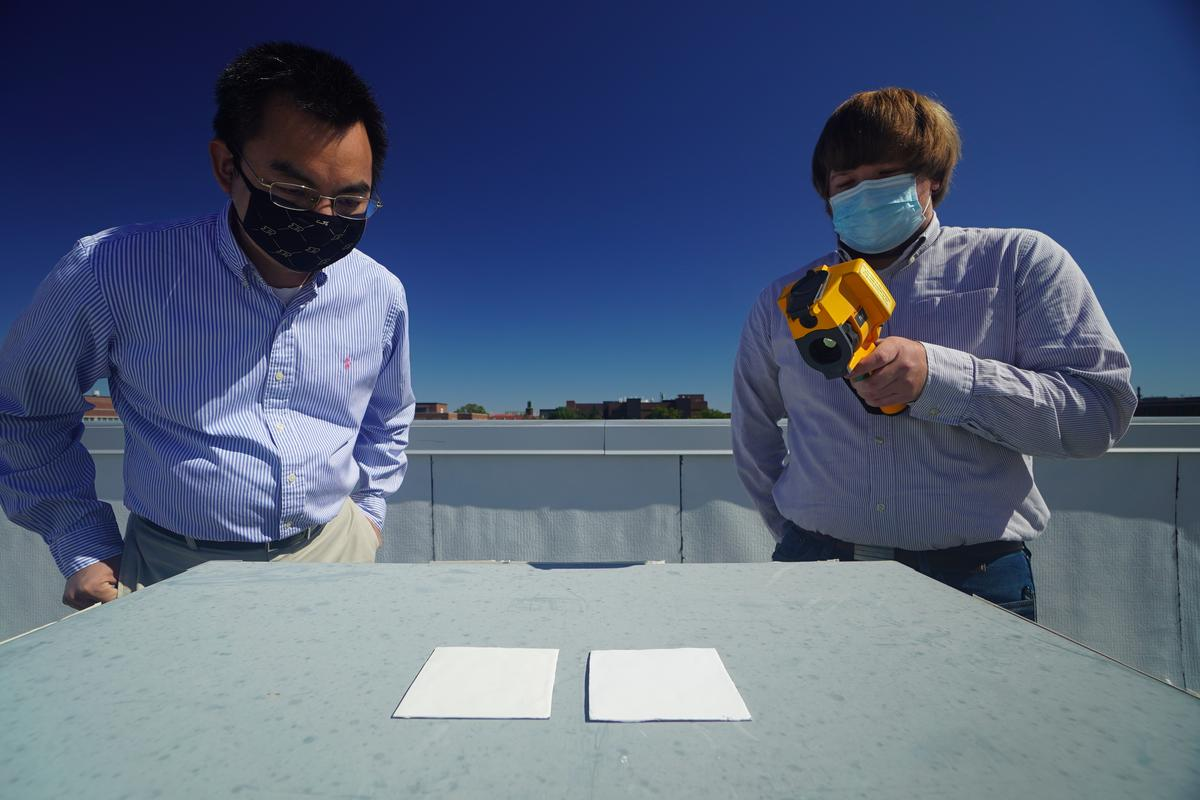 Xiulin Ruan (left) and Joseph People (right) test out samples of the new cooling paint