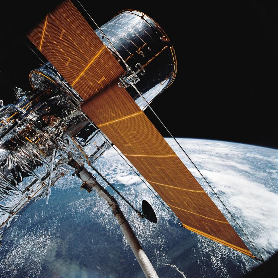 Image of the Hubble Space Telescope in orbit around Earth as seen from the Space Shuttle Discovery during deployment in Apr. 1990