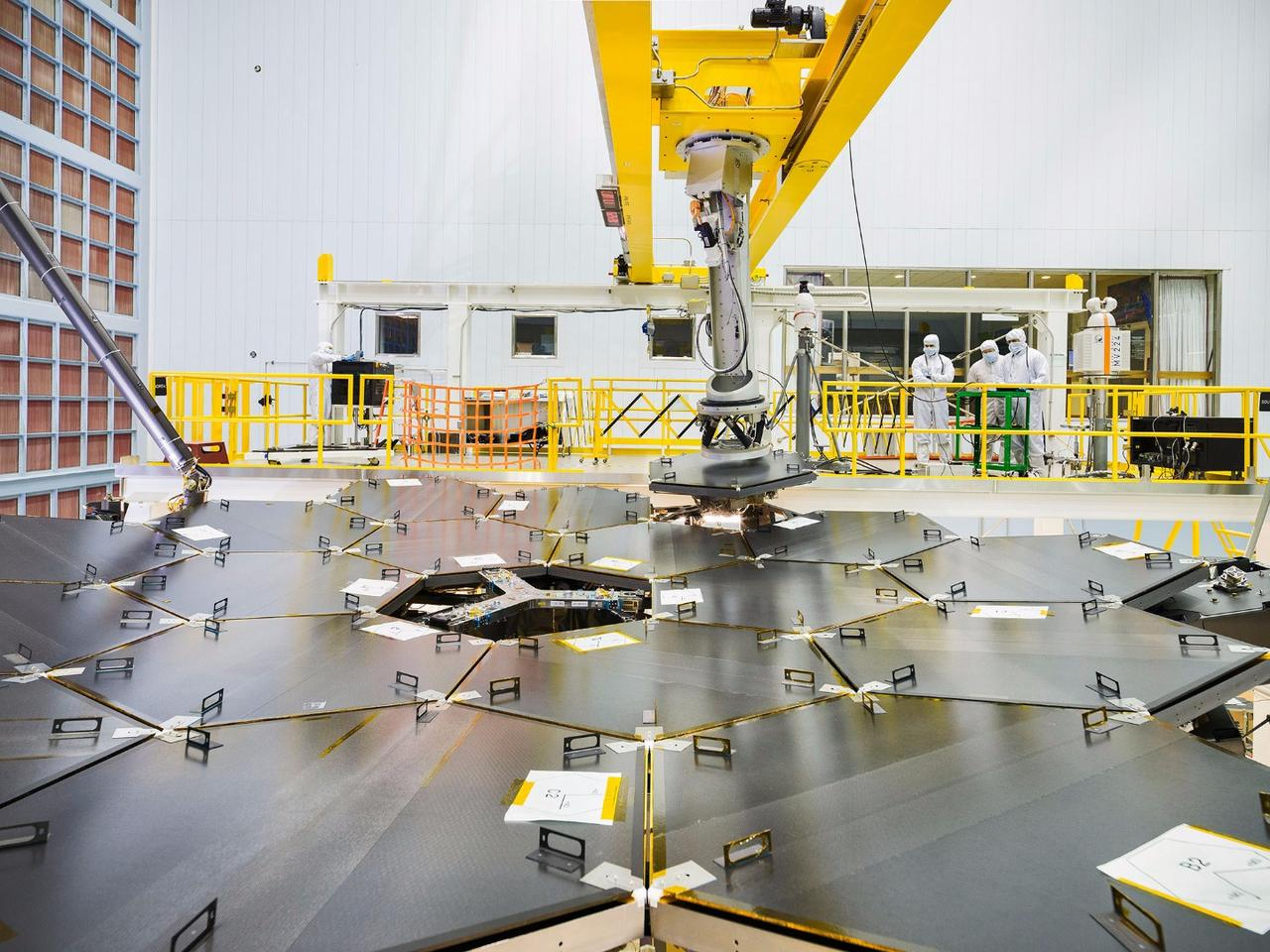 A team of NASA engineers use a robot arm to install the final mirror to the structure of the JWST