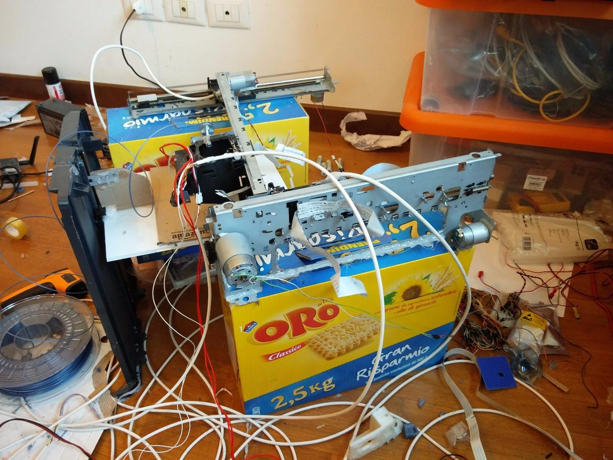 The DIY 3D printer currently stands on cardboard biscuit boxes, but there are plans to make a solid metal frame