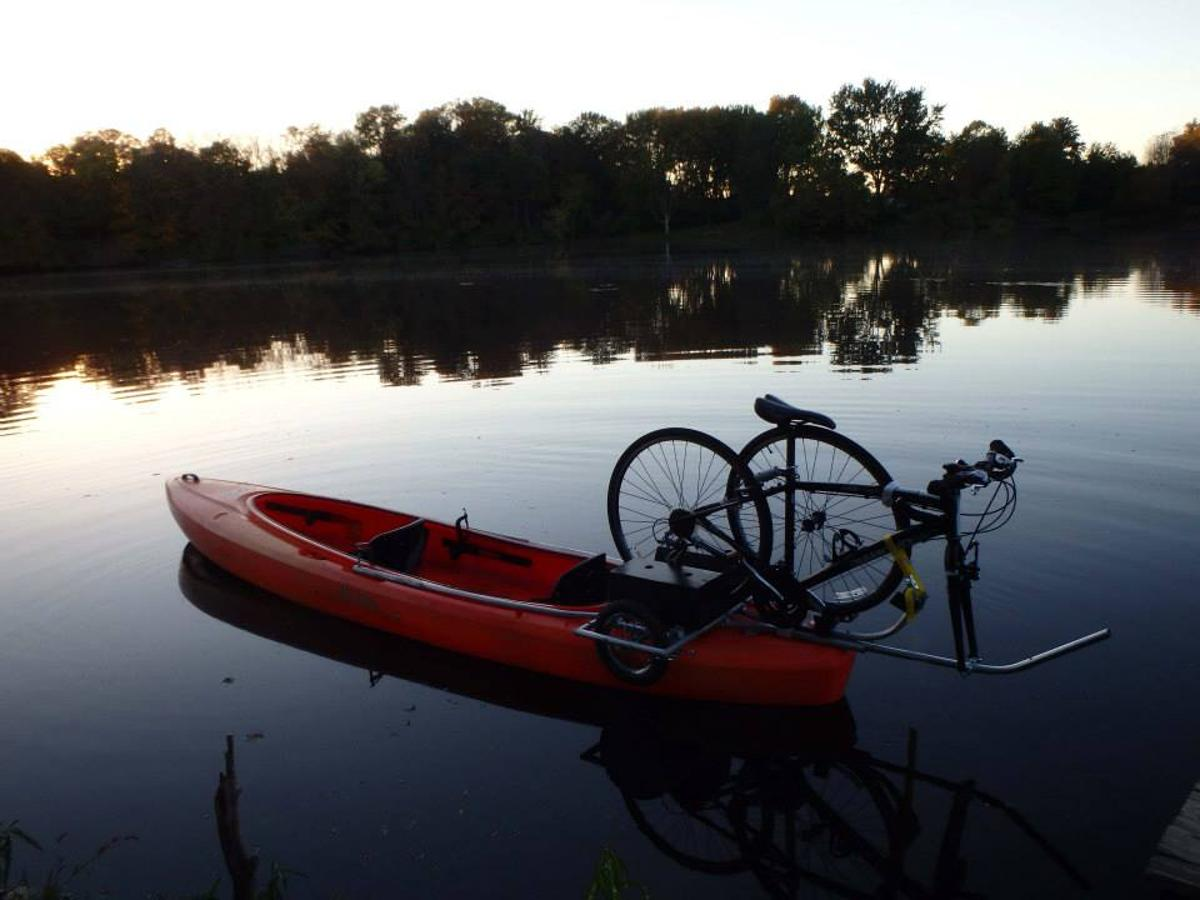 The Solo Shuttle Trailer lets you tow your kayak behind your bike, then mount your bike on your kayak