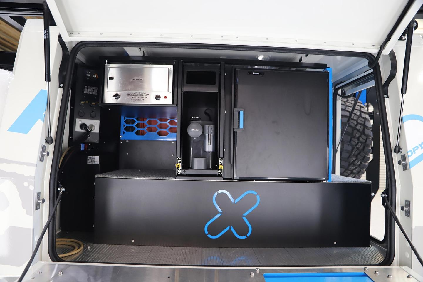 The passenger side of the canopy is dedicated to an available kitchen area with fridge/freezer on the right, coffeemaker in the center, electric oven top left/center, and electrical hardware on the left