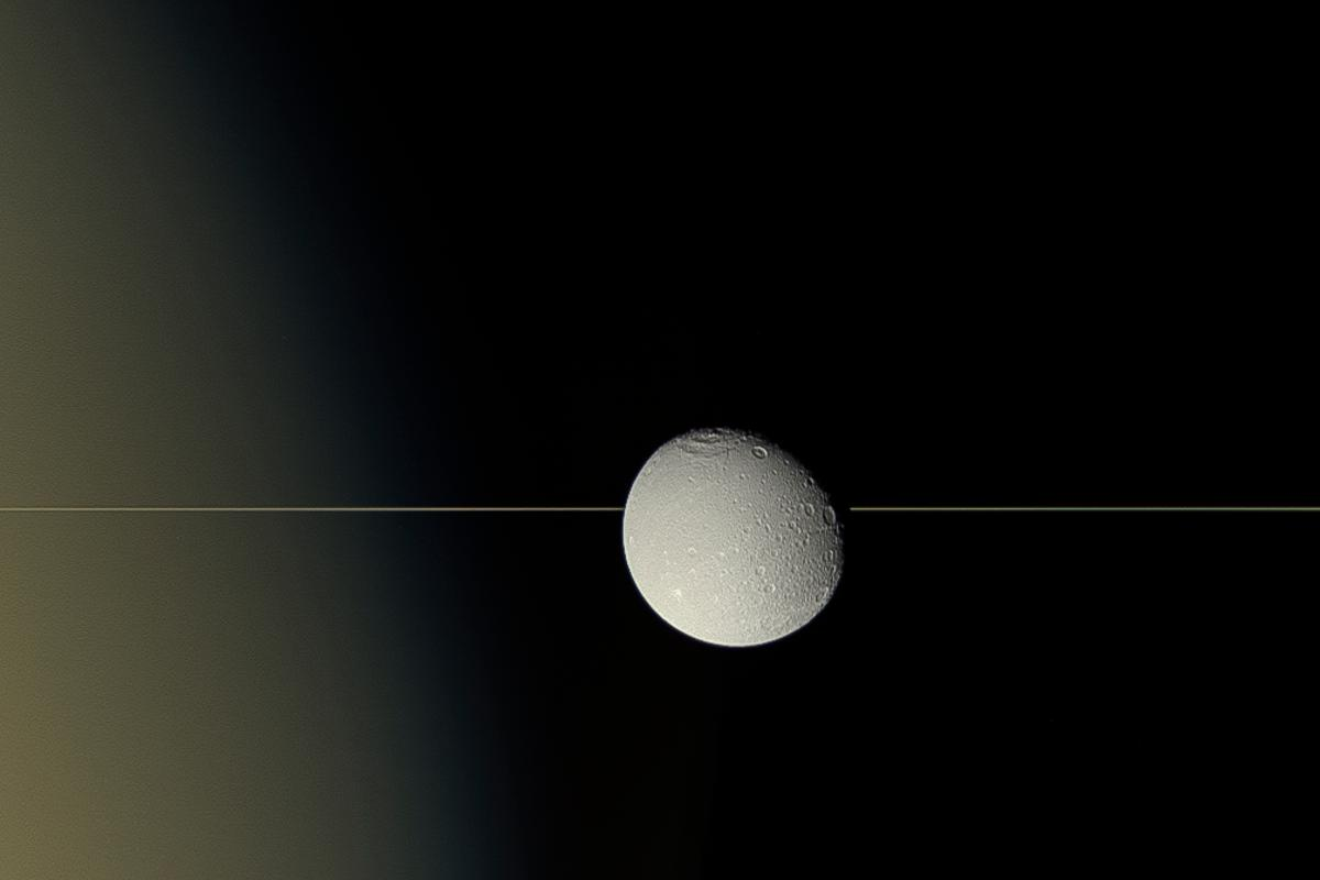 Saturn's moon Dione drifts in front of the planet's iconic rings