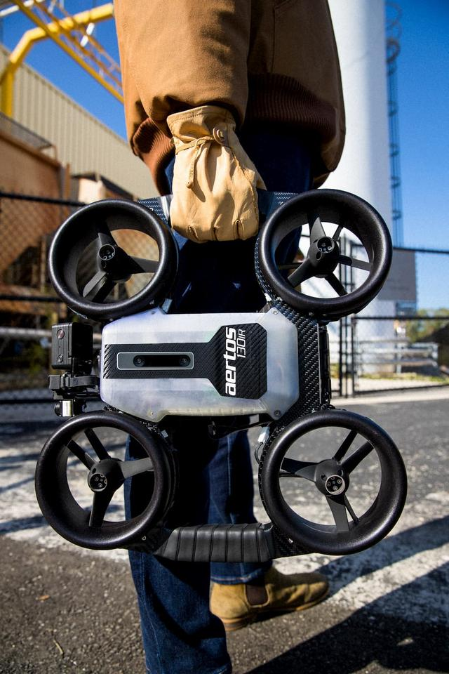 The Aertos 130IR features a carbon fiber composite frame with grip tape-wrapped carrying handles, protective shrouds around its four propellers, and an omnidirectional array of nine sensors