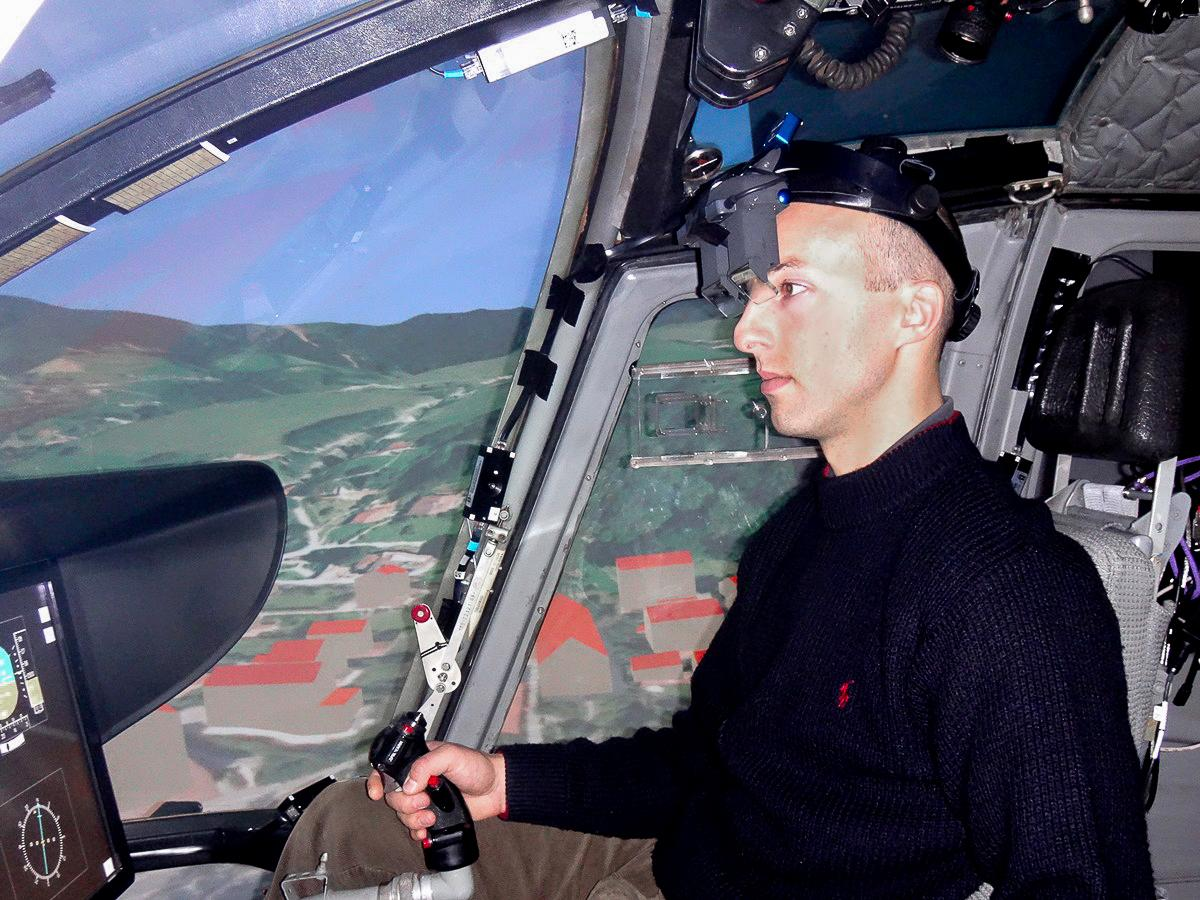 Apilot wearing the augmented reality system inside a helicopter flight simulator