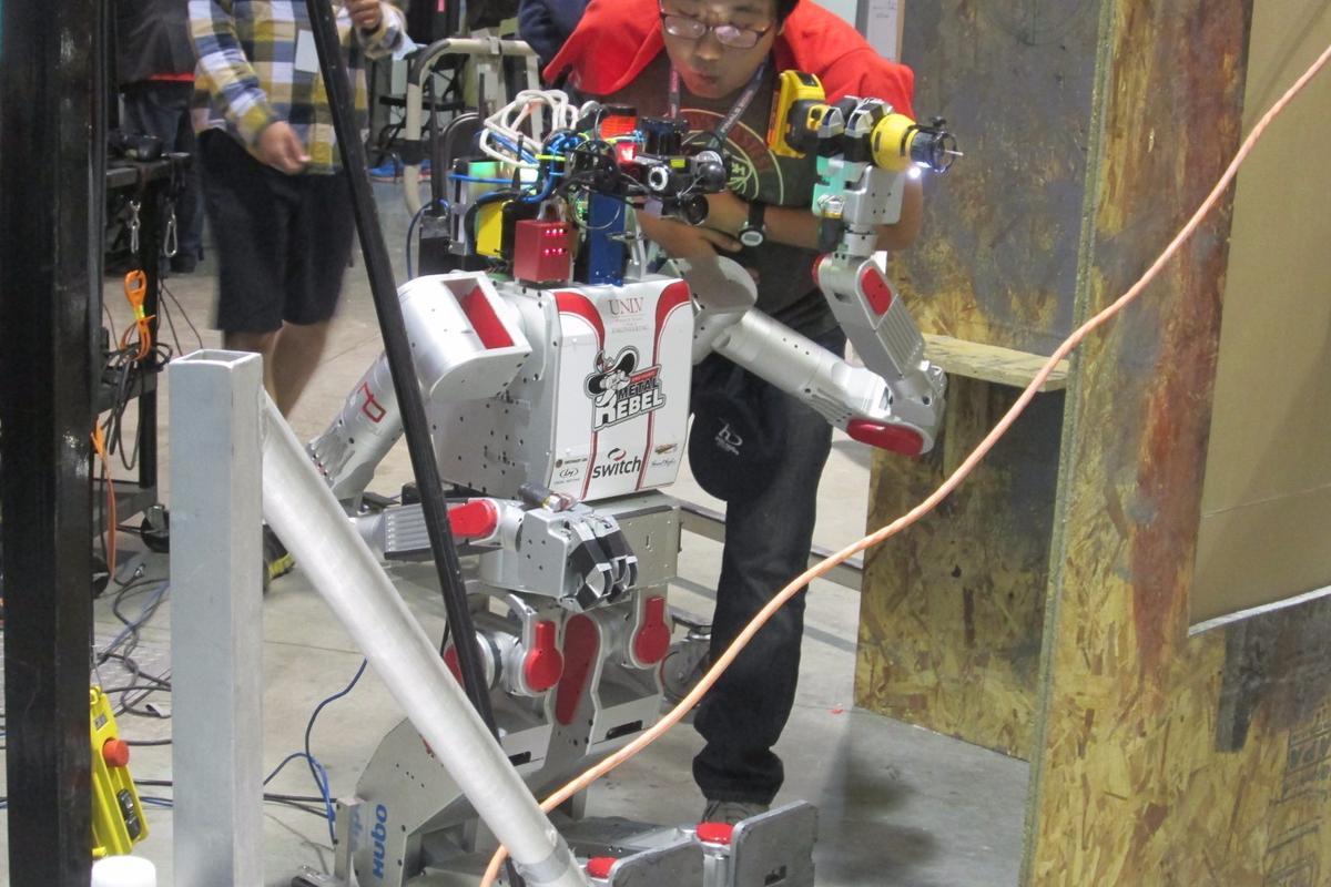 "The robot DRC-Hubo (aka ""Metal Rebel"") receives some TLC at the DARPA Robotics Challenge"
