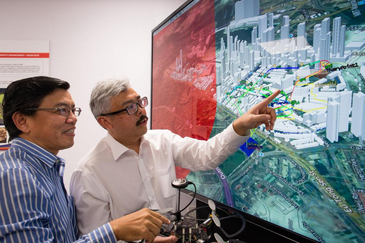 NTU Professor Low Kin Huat (left) and Air Traffic Management Research Institute's Deputy Director Mr Mohamed Faisal Bin Mohamed Salleh discussing an NTU-developed air traffic simulation, which takes into account various solutions to enable safe and efficient drone travel in Singapore.