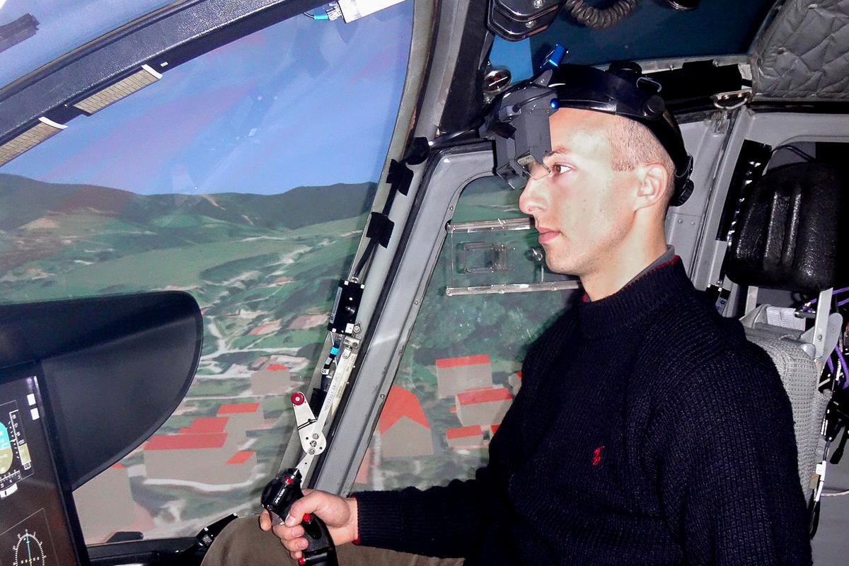 A pilot wearing the augmented reality system inside a helicopter flight simulator