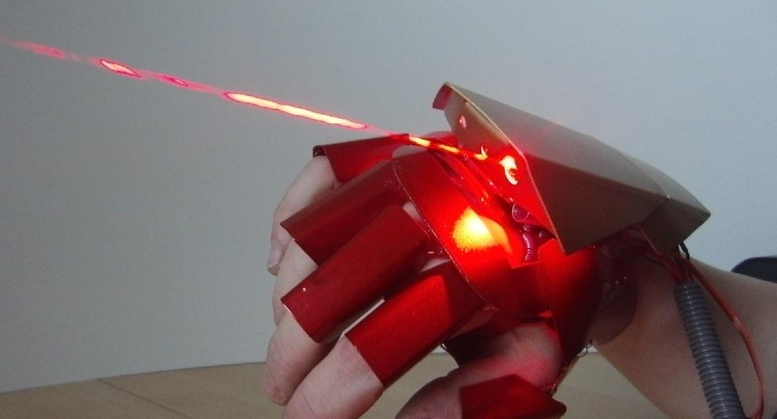 The glove features burning lasers on the top and in the palm