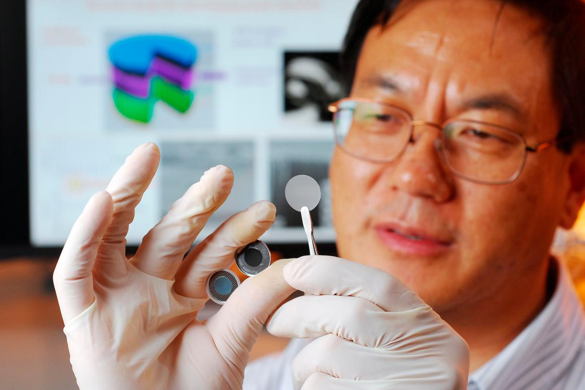 Georgia Tech researcher Zhong Lin Wang holds the components of a new self-charging power cell that uses piezoelectric materials to directly convert mechanical energy to chemical energy (Georgia Tech Photo: Gary Meek)