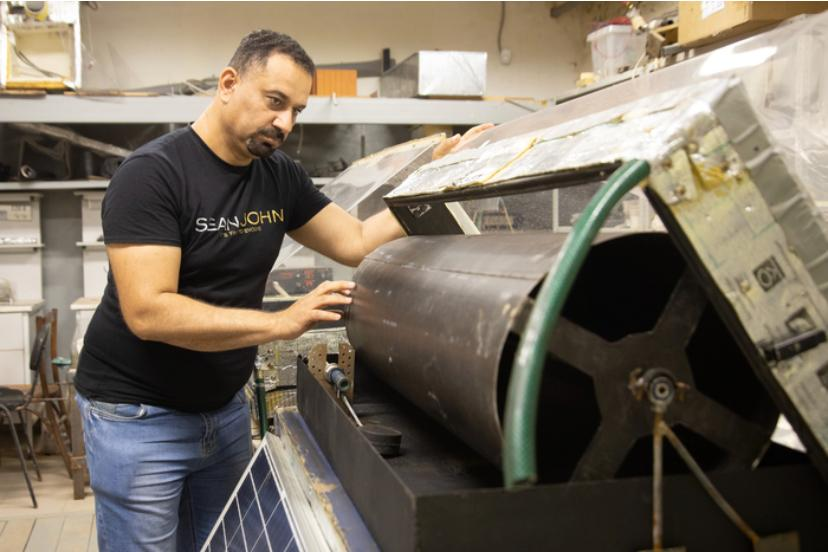 Research engineer Alharbawi Naseer Tawfiq Alwan works with the prototype solar still