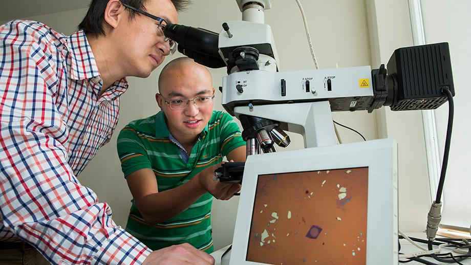 Student Jiong Yang (left) looks at the world's thinnest lens which measures just 6.3 nanometers thick