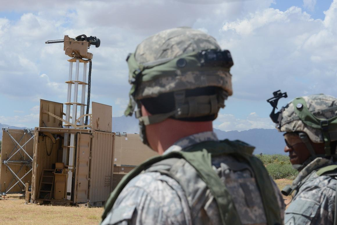 Lieutenant Colonel Raphael Heflin, right, commander, 142nd Combat Service Support Battalion, 1st Armored Division, and another soldier pass near a remotely-controlled weapons system