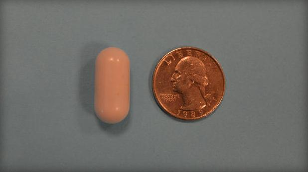 One of the vibrating capsules, with a quarter for scale (Photo: Digestive Disease Week)