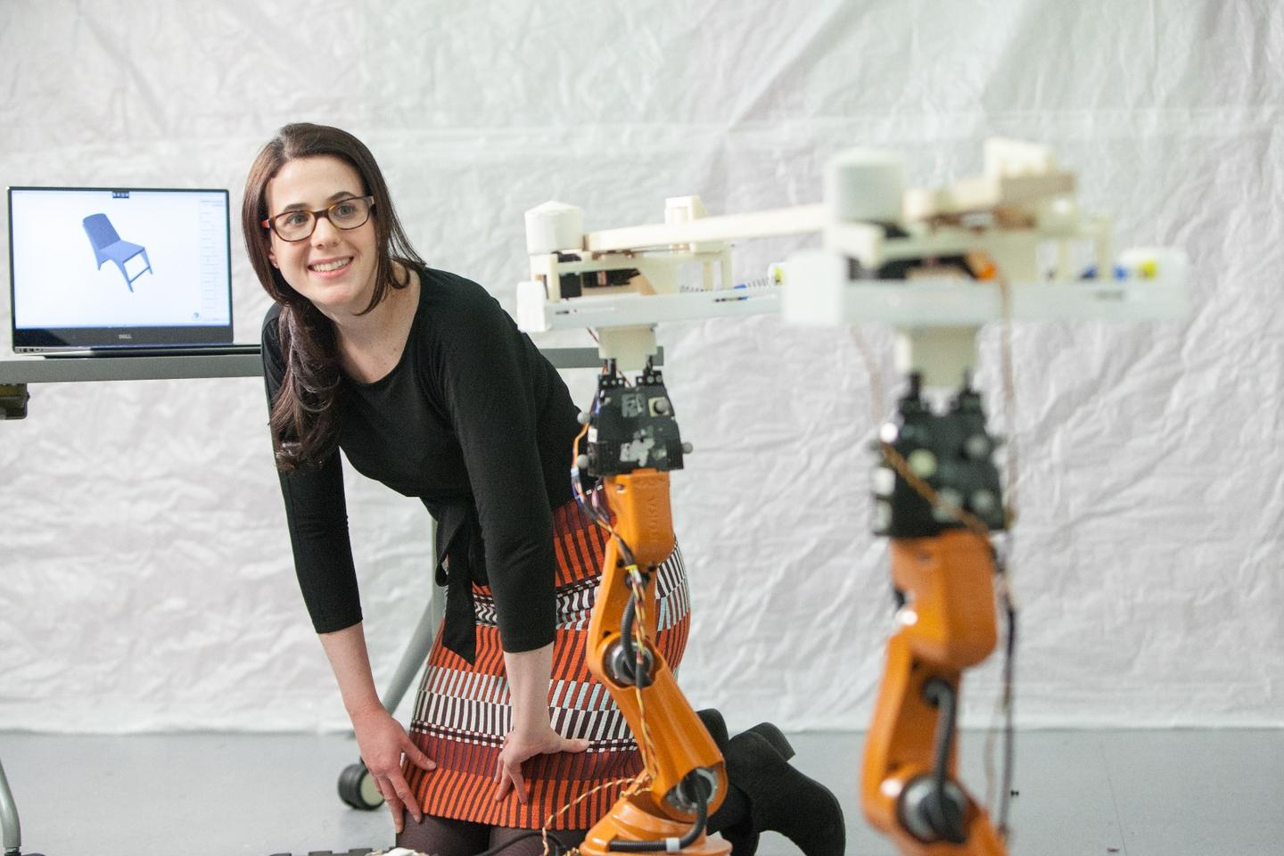 Adriana Schulz watches as the Kuka Youbots bring a piece of lumber to the chop saw