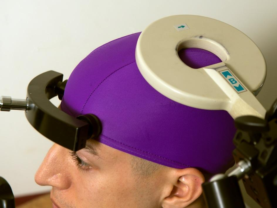 A transcranial magnetic stimulation coil located above the part of the brain that controls hand movements (Photo: Mary Levin, University of Washington)