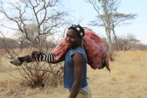 A Hadza man with a chunk of zebra