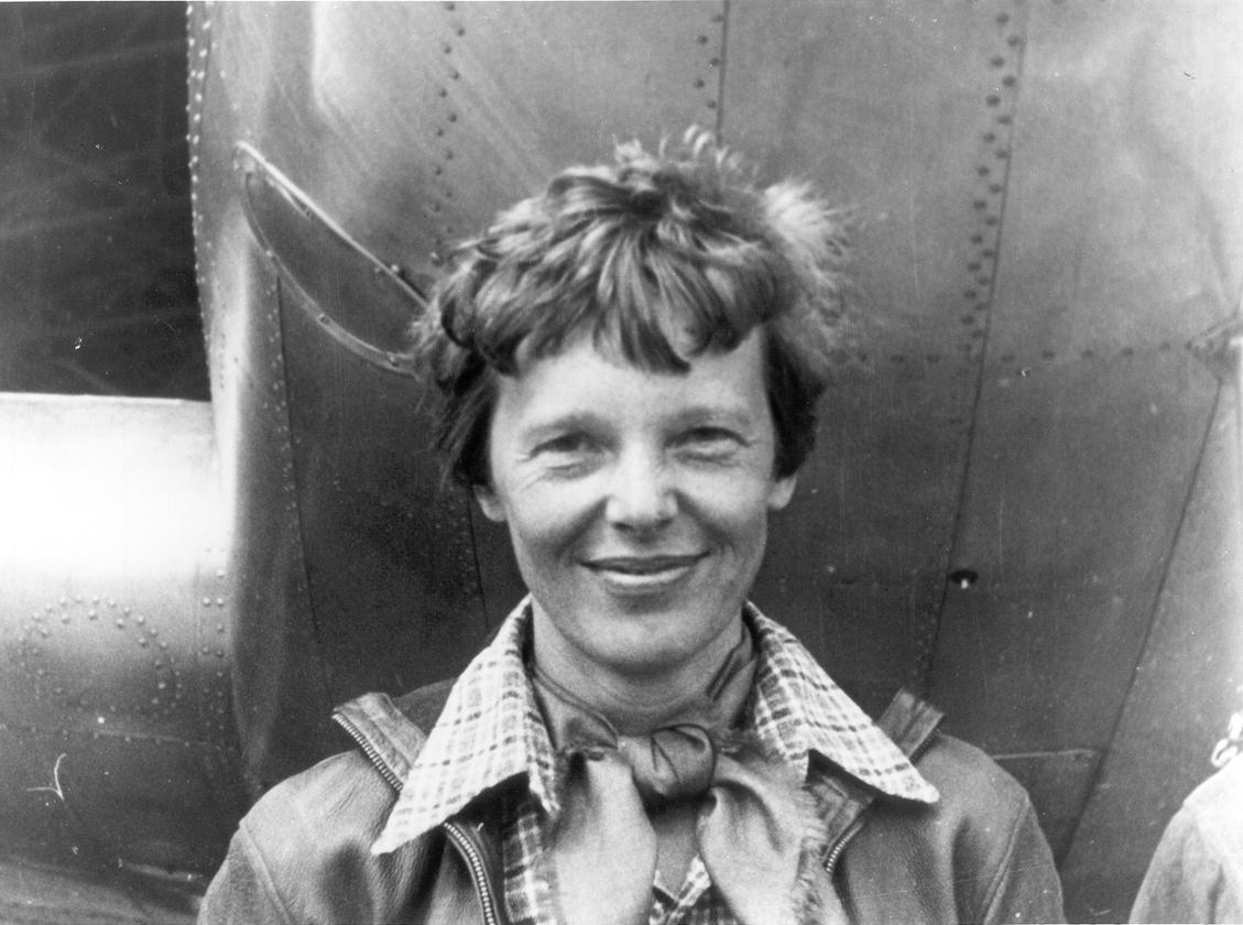 Amelia Earhart, standing under the nose of her Lockheed Model 10 Electra aircraft
