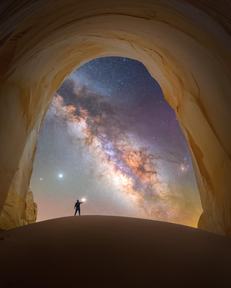 Chamber of light, taken in Utah, USA. Here, a lone figure marvels at the Milky Way framed by the smooth stone walls of a natural chamber beneath the cliffs of Grand Staircase-Escalante.