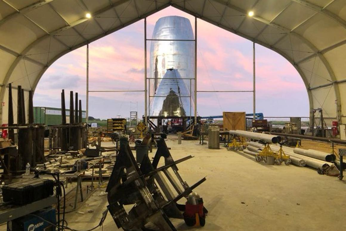 SpaceX's Starship prototype under construction, with a landing leg frame in the foreground