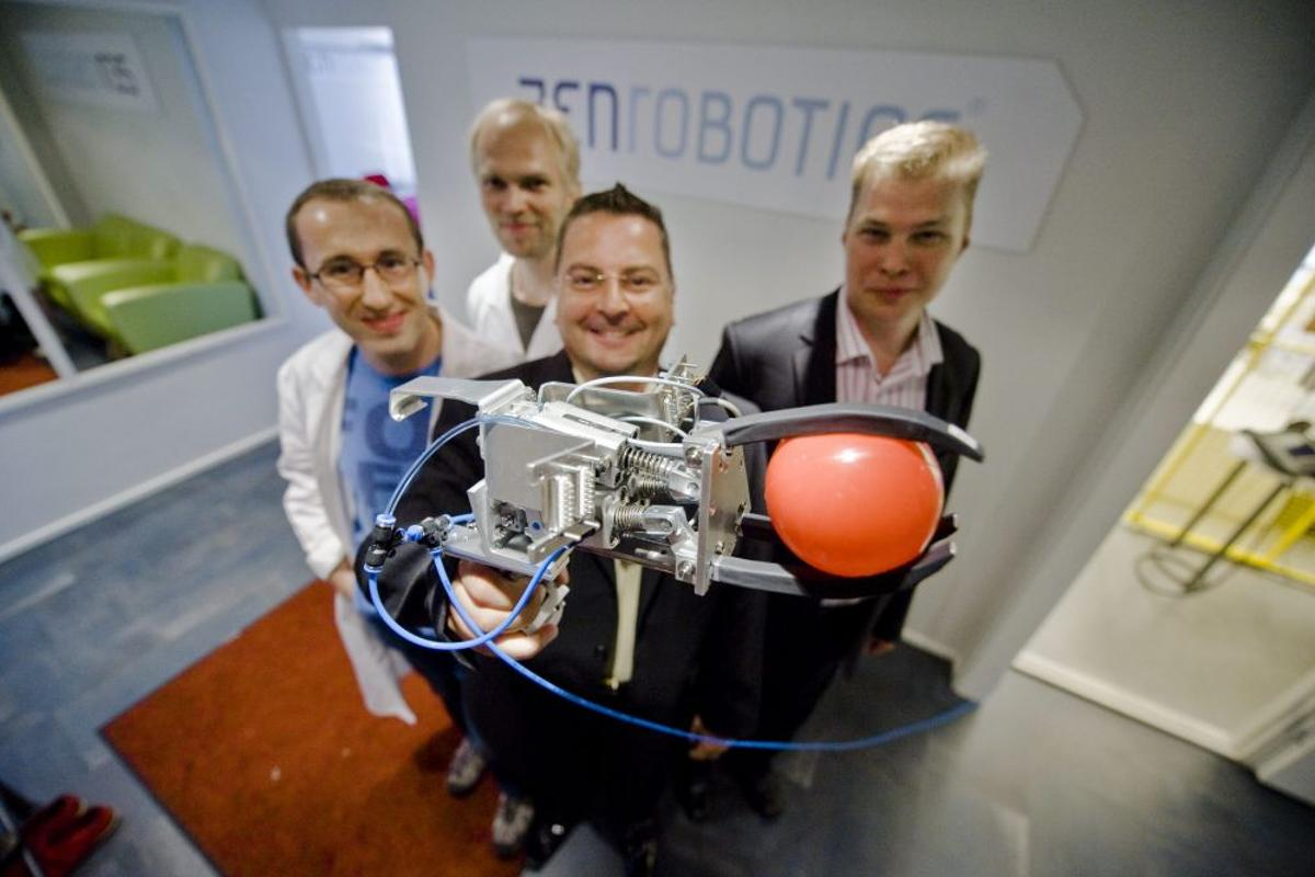 ZenRobotics staff, with the Recycler robot's picking hand(All images courtesy ZenRobotics)