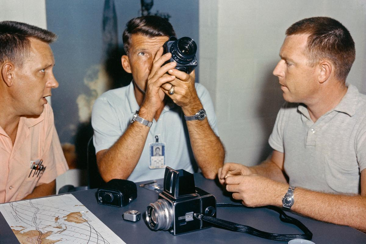 Wally Schirra examines the Hasselblad camera alongside Deke Slayton (L), and Gordon Cooper