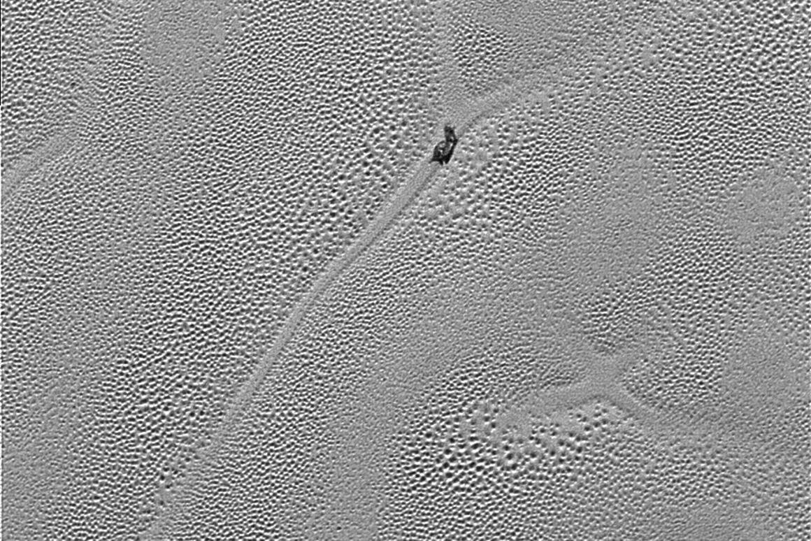 High-resolution image of Sputnik Planum, displaying an x-like artifact in the ice that may in the past have been the joining point between four cell structures