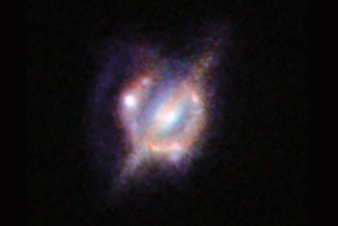 The foreground galaxy can be seen cutting across the lensing light from the distant merging galaxies (Image: ESO/NASA/ESA/W. M. Keck Observatory)