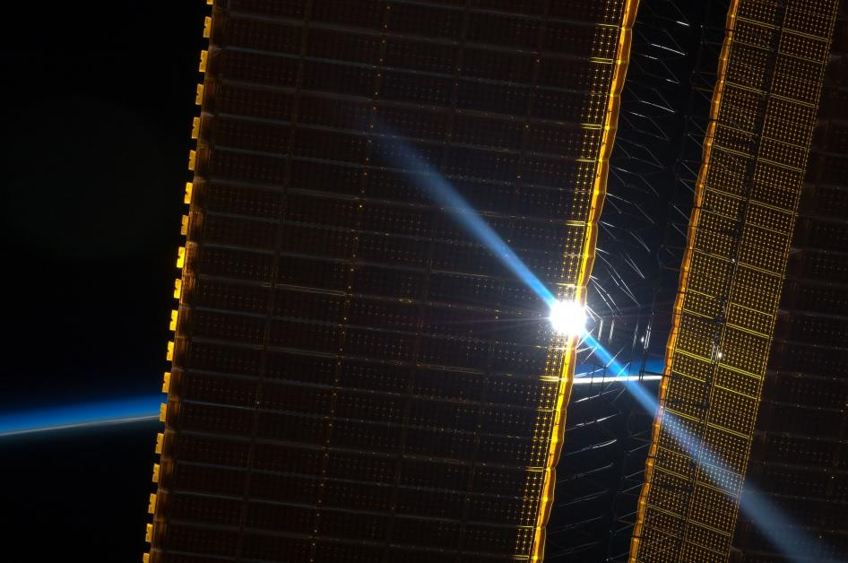 The Sun peeking through one of the ISS's current solar array panels, captured back in June 2012