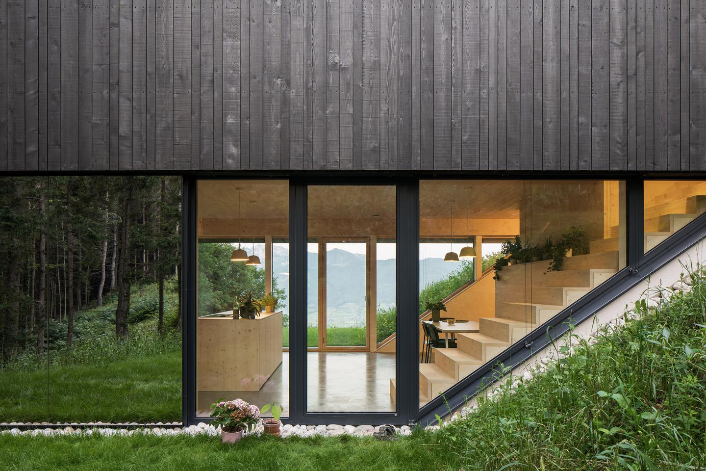 The Mountain House occupies a sloping plot of land in Upper Austria, with thick forest to one side and expansive valley views on the other