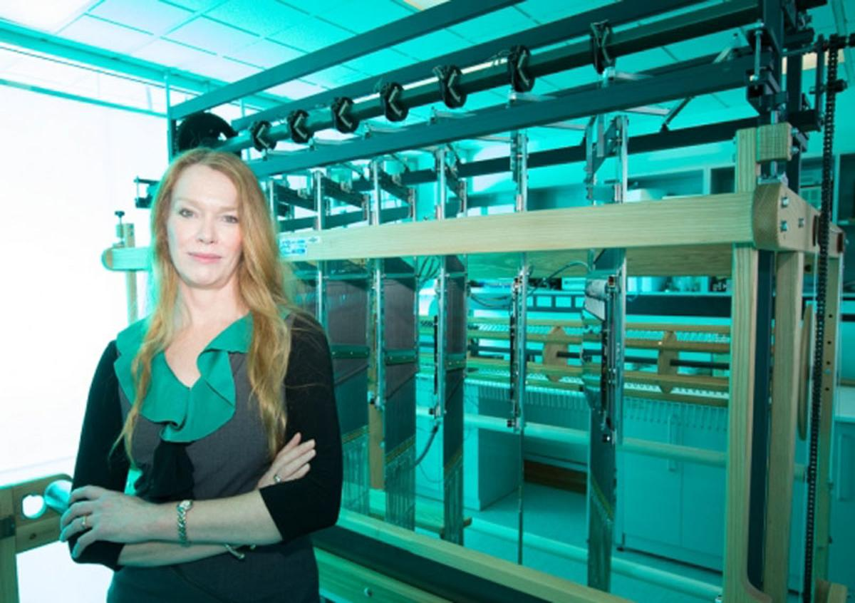 "Professor Melissa Knothe Tate with the computer-controlled jacquard loom used to create a ""smart"" fabric that mimics the properties of periosteum"