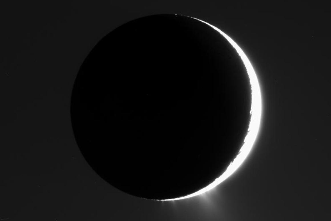 Enceladus passes in front of the Sun, showing off its icy plumes, as captured by the Cassini probe in 2007