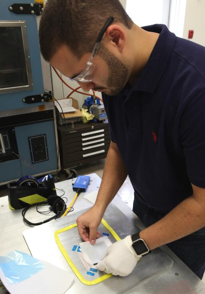 Daniel Perez, from the University of Miami, makes the outer layers for the batteries by compressing carbon fiber