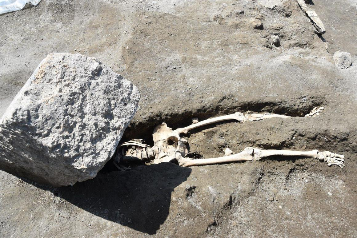 Archaeologists have uncovered the 2,000-year-old skeleton of a man crushed beneath a huge stone block, while trying to flee the volcanic eruption that wiped out Pompeii