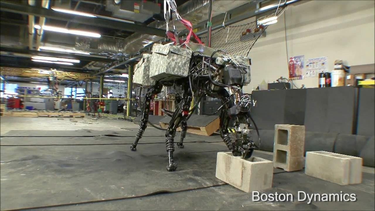 Boston Dynamics' quadruped robot BigDog grabs a cinder block from the floor using its new arm attachment