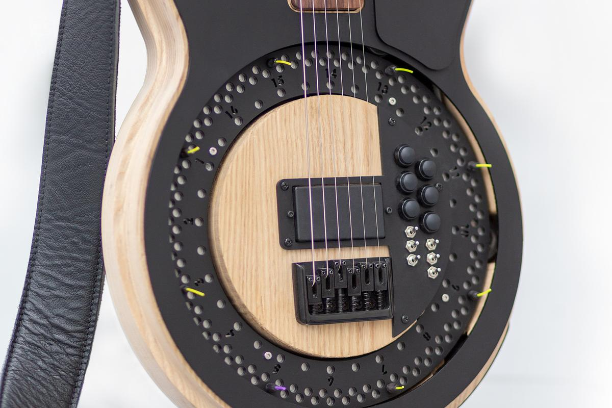 The motor-driven disc has guitar picks attached to it, which strike the strings when it spins up