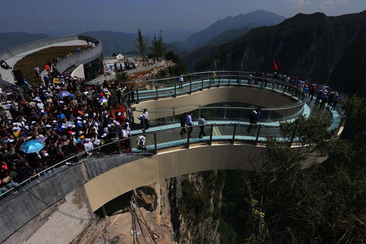 The world's longest glass-bottomed cantilever skywalk has tourists contemplating a 718 m (2,356 ft) drop to the rocks below (Photo: Imaginechina)