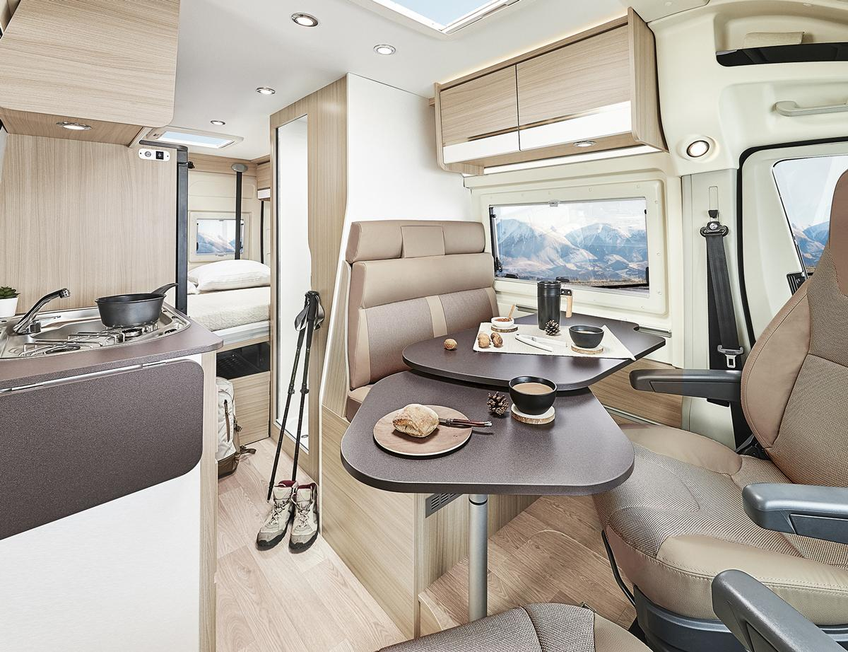 The interior is a classic layout with driver-side dining area and bathroom, passenger-side kitchen, and rear bedroom