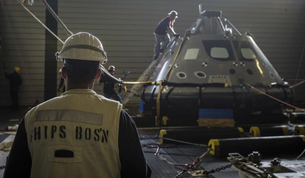 Chief Warrant Officer 4 Kelvin Dooley inspects Orion dummy capsule in recovery well of USS San Diego