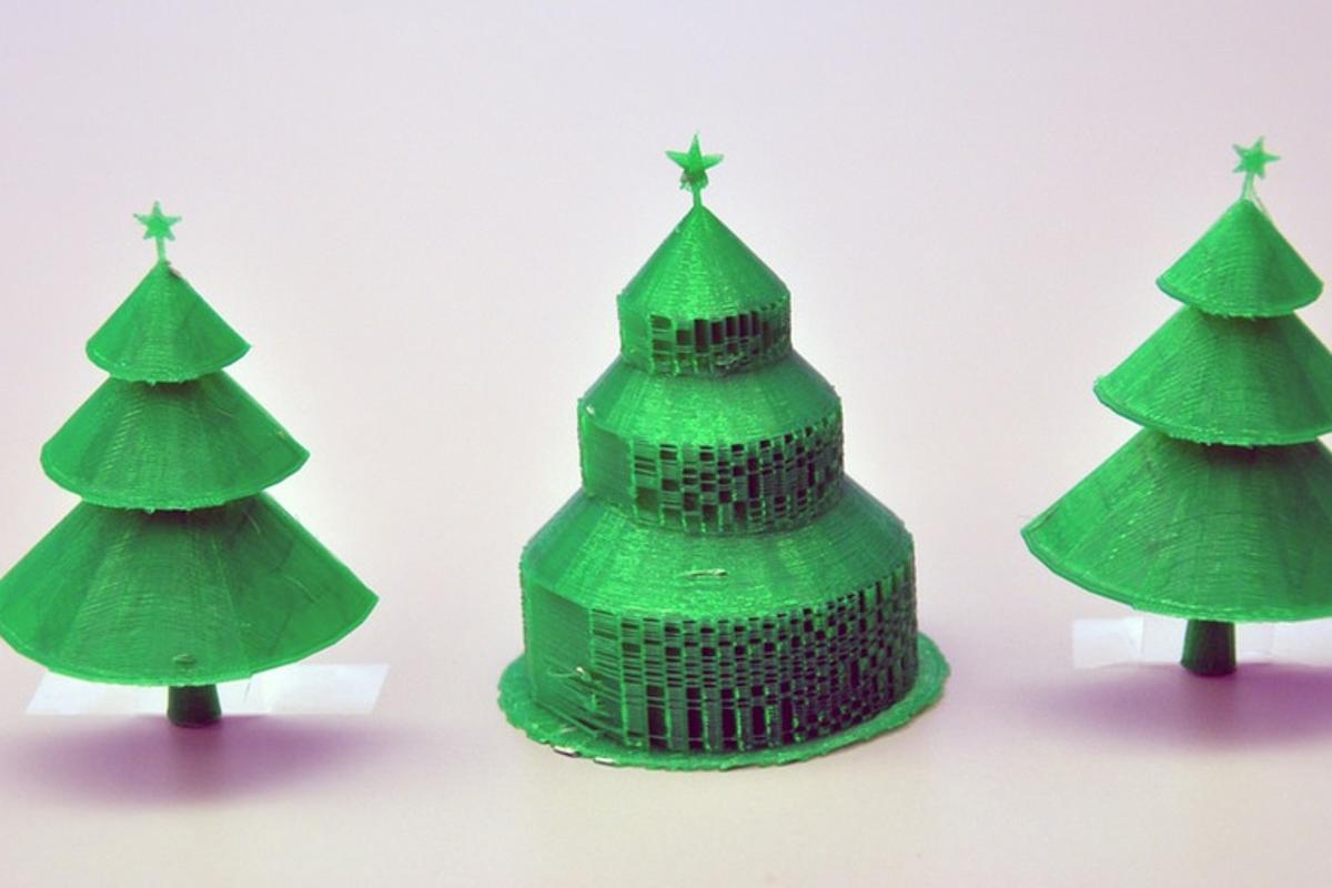 The Christmas tree in the center was 3D-printed in the traditional manner, and displays the extra material to support each branch. Beside it are the two halves of the same tree printed using the new algorithm, with no supportive material to remove (Photo: Simon Fraser University)