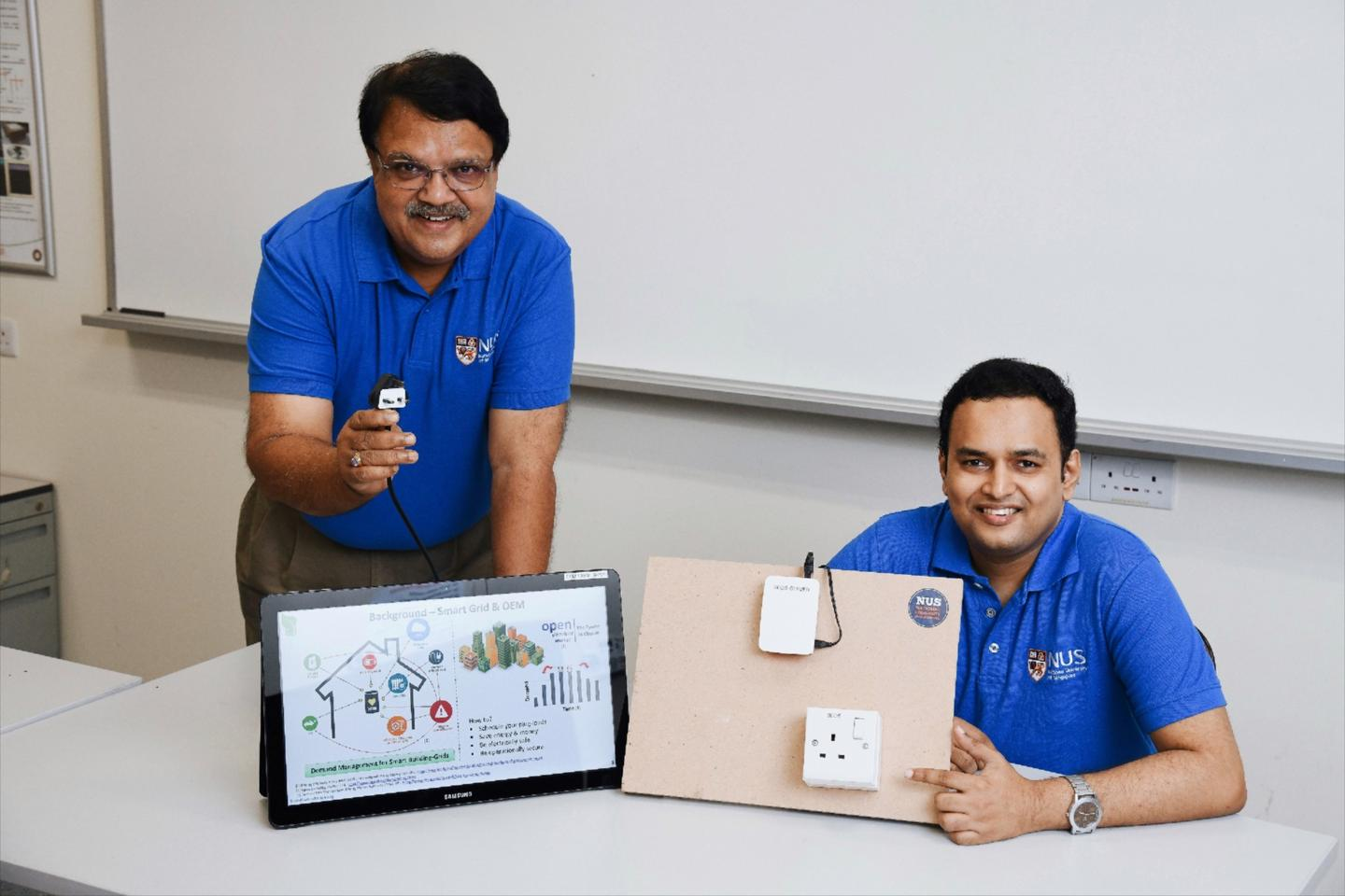 Assoc. Prof. Sanjib Kumar Panda (left) and Dr. Krishnanand Kaippilly Radhakrishnan with a prototype of the Smart Electrical Outlet/Socket (SEOS) system