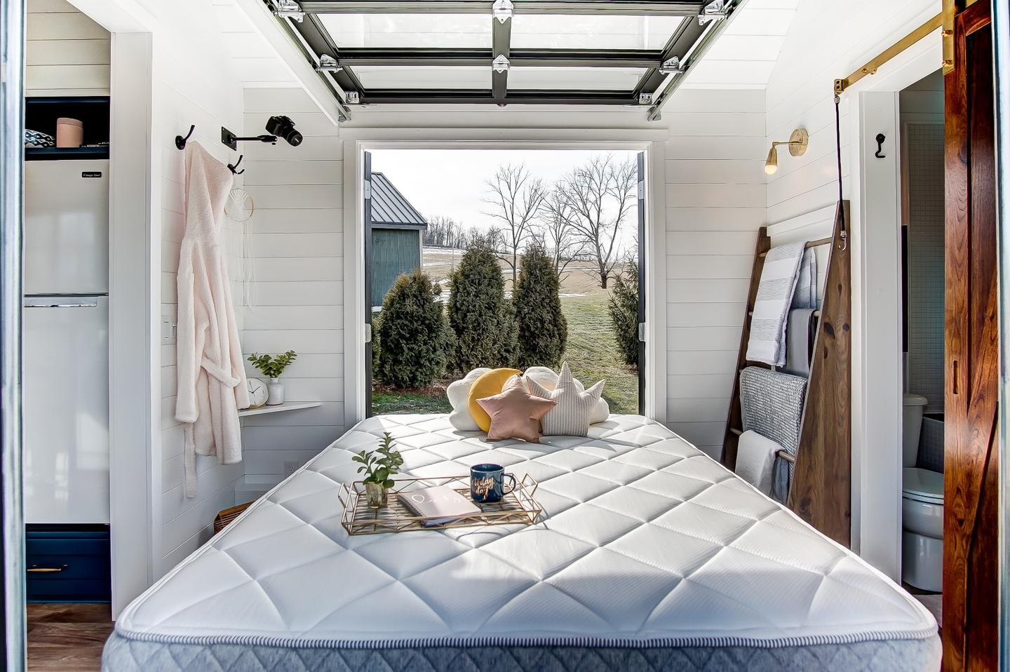The Allswell Tiny Home's bedroom opens to the outside with a garage-style door