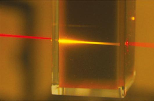Red light from a laser pointer is converted into higher-energy yellow light as it passes through the liquid photochemical upconverter (Photo: University of Sydney)